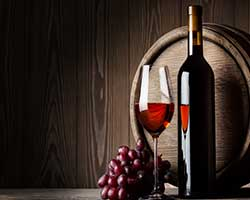 Wine glass and wine bottle with grapes in front barrel thumbnail